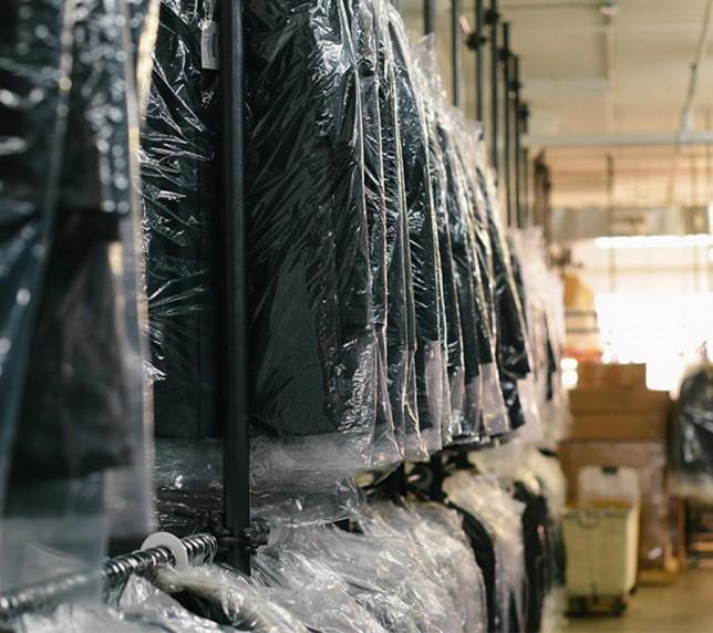 Muncitori la sortarea hainelor în depozite.